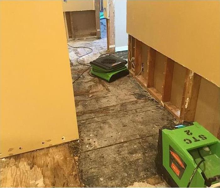 Walls with water damage and green equipment.